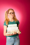 Curious, naughty, playful schoolgirl with stack of books and big Stock Photography