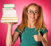 Curious, naughty, playful schoolgirl with stack of books and big Royalty Free Stock Images