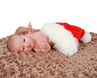 Curious newborn laying in Santa hat on blanket Royalty Free Stock Images