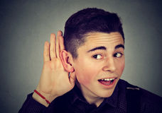 Curious nosy man with hand to ear listening to gossip conversation Royalty Free Stock Images