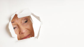 Curious older woman looking through hole at copy space Stock Photography