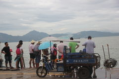 Curious onlookers shore fishing boat people Stock Photos