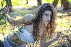 Curious pagan girl looking through the branches into the camera.  Royalty Free Stock Photo