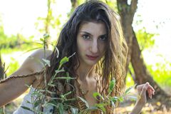 Curious pagan girl looking through the branches into the camera.  Royalty Free Stock Photography
