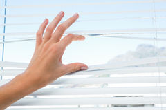 Curious person watching through venetian blind Stock Photo