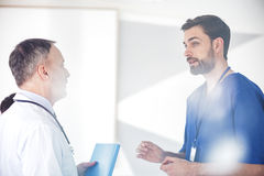 Curious physician considering with partner during conference Stock Image