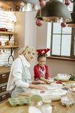 Curious pretty girl peeking into hot own and her baking cookies royalty free stock photos