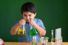Curious pupil. Curious boy smelling colored liquid in the flasks in science class Royalty Free Stock Photo