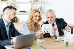 Curious realtor pointing to the little house while sitting with his colleagues Royalty Free Stock Image