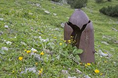 Curious remnants of warlike times. Remnants of warlike times - destroyed artillery projectile at 1600 meters altitude in the Lalider Valley in Tyrol Stock Images