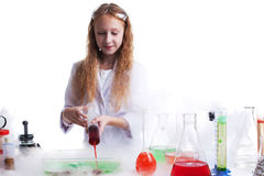 Curious schoolgirl mixes reagents in studio Royalty Free Stock Photos
