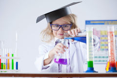 Curious schoolgirl pouring reagent into flask Stock Image