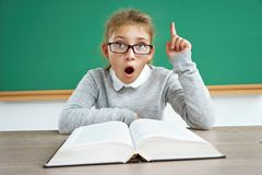 Curious schoolgirl reads book. Photo of astonished little girl wearing glasses, pointing finger up. Education concept royalty free stock photo