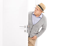 Curious senior looking at something behind a door. Curious senior gentleman looking at something behind a white door isolated on white background Royalty Free Stock Photos