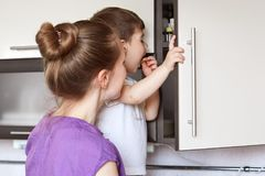 Curious small boy looks with great interest in kitchen shelf, tries to find something, being naughty, affectionate mother stands b. Ack to camera, tries to have Royalty Free Stock Image