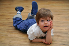 Curious small boy lying on wooden floor royalty free stock image