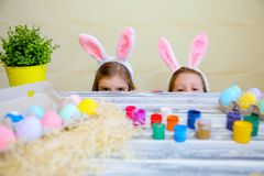 Curious small girls in bunny ears peeking out from behind kitchen table with tasty easter eggs and looking at camera stock image