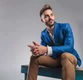 Curious smart casual man sitting on blue wood bench and praying royalty free stock photography