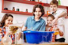 Curious smart children pouring chemical liquids in a washbowl. What will happen. Curious smart positive children standing around a washbowl and pouring chemical Royalty Free Stock Image