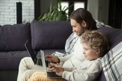 Curious smiling son with dad using laptop looking at screen. Curious smiling child typing on laptop looking at screen with dad on sofa, daddy and little boy royalty free stock image