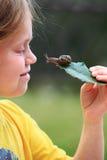 Curious snail. On a leaf and a child's face stock photos