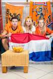 Curious Soccer Fans Watching Match At Home. Curious young Dutch soccer fans watching match at home Stock Photo