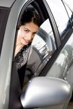 Curious stare. Portrait of vivid brunette looking with interest through the window of her car Stock Images