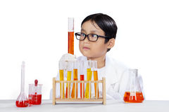 Curious student doing chemical experiment. Portrait of curious little student makes chemistry experiment by using test tube and chemical fluid, isolated on white Stock Images