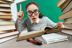 Curious student reads a books. Did you know that?! Curious student reads a books. Photo of astonished young girl wearing glasses pointing finger up. Education Stock Images