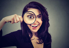 Curious surprised young woman looking through a magnifying glass. Curious surprised woman looking through a magnifying glass royalty free stock image