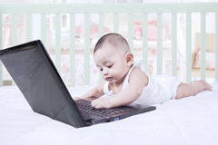 Curious toddler playing laptop on bed Royalty Free Stock Image