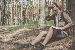Curious traveler is inspecting area of land. What is there. Side view full length of pleasant young tourist is resting on the ground in forest. He is holding map Stock Images