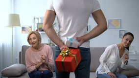 Curious wife and mother-in-law looking at man holding gift boxes behind back. Stock footage stock video footage