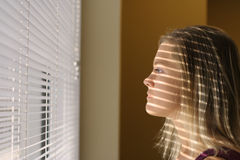 Curious woman 3. Womand with a shadow from blinds over her face Royalty Free Stock Photos