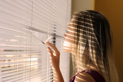 Curious woman. Woman looking though blinds out of window Royalty Free Stock Image