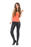 Curious Woman Full Length. Young woman in orange shirt, leather trousers and boots standing and looking away. Full length studio shot isolated on white stock image