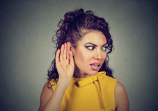 Curious woman with hand to ear secretly listening to gossip Stock Images