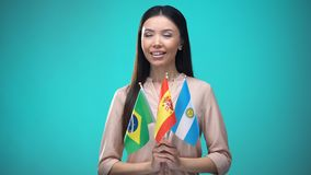 Curious woman holding Brazil, Spain and Argentina flags, learning language. Stock footage stock video footage