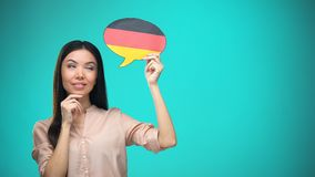 Curious woman holding German flag sign, learning language, education abroad. Stock footage stock video footage