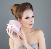 Curious Woman Holding Gift Box with Pink Ribbon. Surprise Stock Image