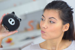 Curious woman holding piggy bank Stock Images