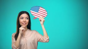 Curious woman holding USA flag sign, learning language, education abroad. Stock footage stock video