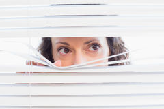 Curious woman looking through blinds Royalty Free Stock Photos