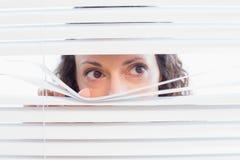 Curious woman looking through blinds Royalty Free Stock Photos
