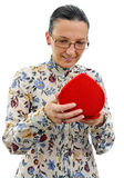 Curious woman looking at gift in red heart box Royalty Free Stock Photography