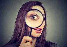 Curious woman looking through a magnifying glass. Curious young woman looking through a magnifying glass stock image