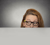 Curious woman peeking over edge of blank empty paper billboard Royalty Free Stock Photography
