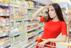 Curious Woman Shopping  at The Supermarket. Portrait of a young girl in a market store with a shopping cart Stock Image