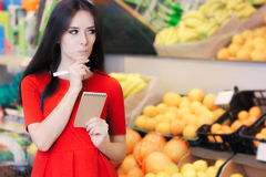 Curious Woman in The Supermarket with Hopping List. Young girl in a market store with a shopping list thinking what to buy stock photo