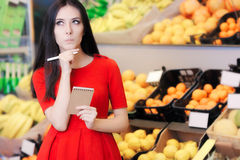 Curious Woman in The Supermarket with Hopping List. Young girl in a market store with a shopping list thinking what to buy Stock Images